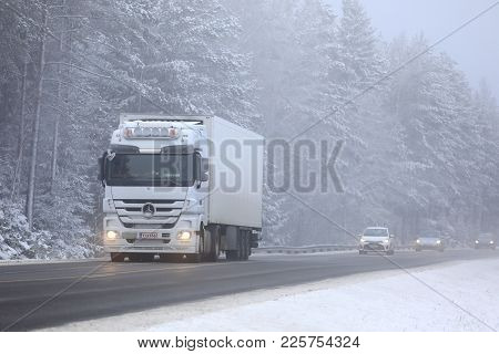 Salo, Finland - January 20, 2018: White Mercedes-benz Actros Semi Trailer Transports Goods Along Fog