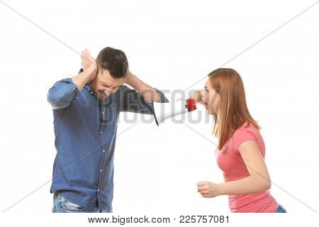 Angry woman with megaphone scolding her husband on white background