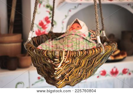 Antique Doll Lying In A Wooden Vintage Cradle
