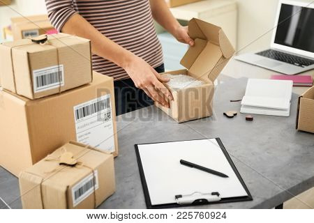 Young woman preparing parcels for shipment to customers at table in home office. Startup business