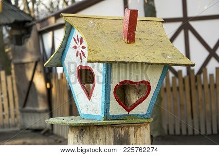 Colorful Bird Feeder. Creative Tree House With Food For Avian In Winter. Countruyside House Exterior