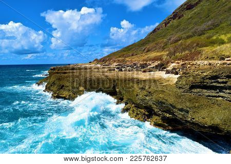 Waves Crashing Onto Volcanic Lava Rocks Taken On The Rural Rugged Coast At Yokohama Beach In Oahu, H