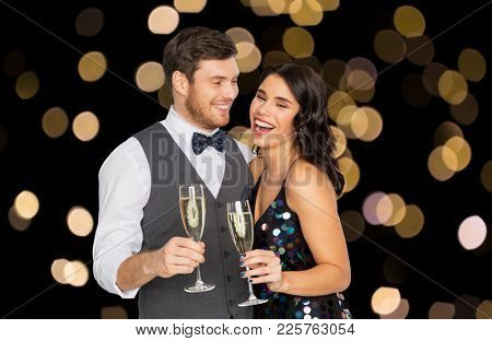 celebration and holidays concept - happy couple with glasses drinking non alcoholic champagne at party over lights on black background