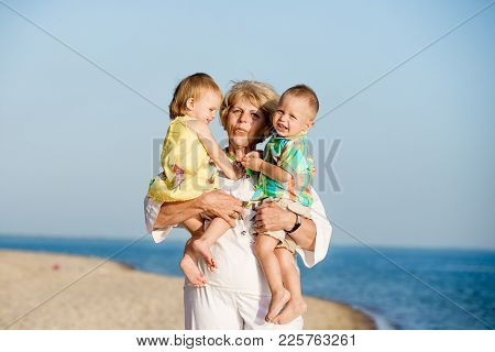 Happy Grandmother Holding Hands On The Grandchildren In The Sammer On The Beach.