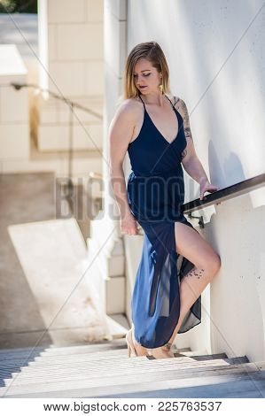 Blonde In Blue Sheer Dress Showing Bare Thigh As She Looks Back Down The Stairs On Sunny Winter Day