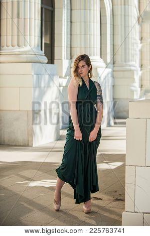 Alternative Blonde Model Standing Among White Stone Columns In Emerald Green Halter Top Gown.  Shot