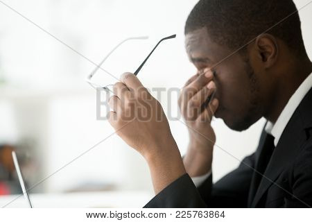 African Tired Businessman Feels Eyestrain Taking Off Optical Computer Glasses, Holding Spectacles In