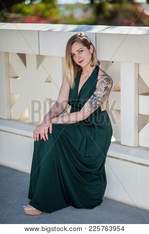 Pretty Blonde Modeling Green Halter Top Gown Seated  Along On Lower Step Of Decorative Walkway Raili