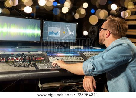 music, technology, people and equipment concept - man at mixing console with computer monitors in sound recording studio over festive lights
