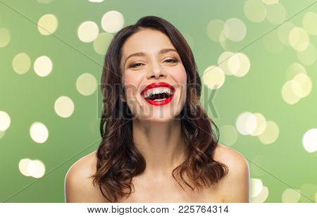 beauty, make up and people concept - happy laughing young woman with red lipstick over green background with lights