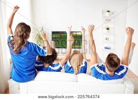 sport, people and entertainment concept - happy friends or football fans watching soccer game on tv and celebrating victory at home