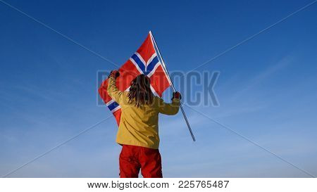 Man with norway flag on the top point. Succesful winer concept.