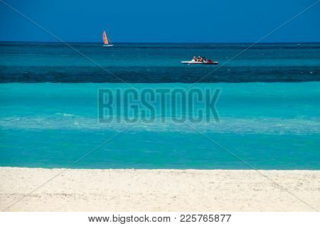 Blue Stripes Of Ocean And Sky On The Cuban Beach With Pedal Boom And Windsurf On Waves.