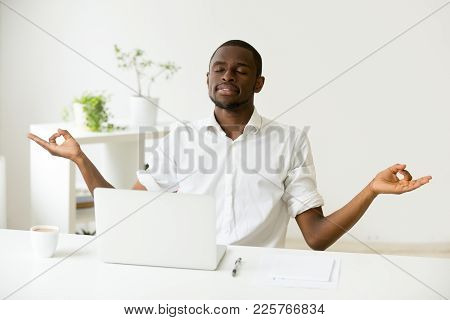 Calm Happy African American Man Meditating At Home Office Desk With Laptop Developing Focus And Conc