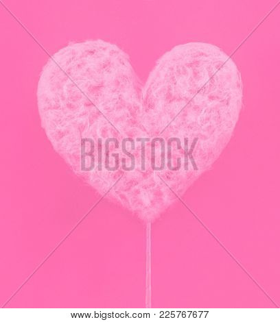 Pink heart made of sweet cotton candy on paper background. Trendy minimal pop art style.