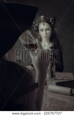 Gothic Horned Girl Eating Worms Over Dark Background