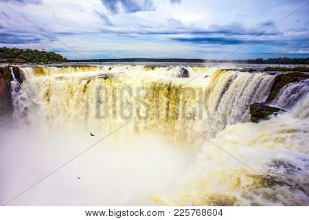 Grandiose waterfalls Iguazu in the rainy season - Garganta del Diablo. A spectacular journey to the grandiose exotic waterfalls on the Parana River. Concept of active and photographic tourism