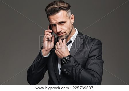 Photo of bearded mature man in busines suit looking on camera while having mobile conversation isolated over dark gray background