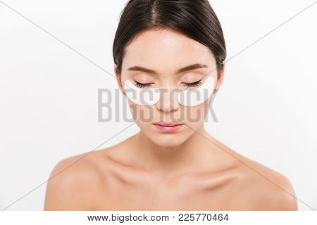 Beauty portrait of relaxed asian woman with brunette hair wearing cosmetic patches under both eyes isolated over white background