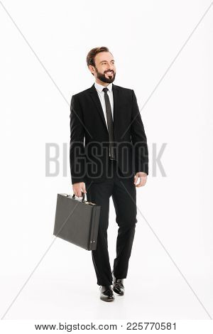 Full-length image of good-looking man in business suit carrying black briefcase and looking aside isolated over white background