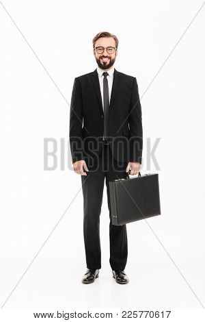 Full-length image of good-looking man in business suit posing with black briefcase and looking on camera isolated over white background