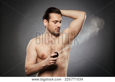 Portrait of a young shirtless man spraying deodorant isolated over gray background