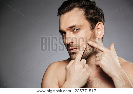 Close up portrait of a concentrated shirtless man squeezing pimple on his face isolated over gray background