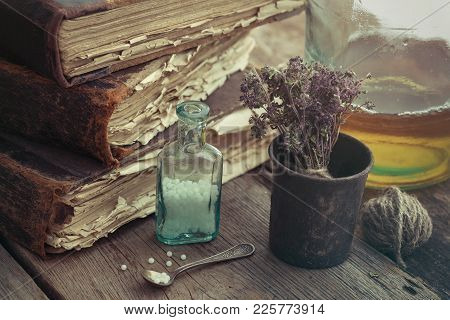 Stack Of Old Books, Vintage Mortar Of Medicinal Herbs, Vial Of Homeopathic Globules And Tincture Bot