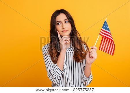 Portrait of a pensive young girl looking away while holding american flag isolated over yellow background