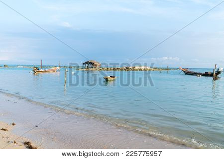 Asian Idyllic Picturesque Coastal Scene With Traditional Long Tail Fishing Boats And Grass Roof Shel