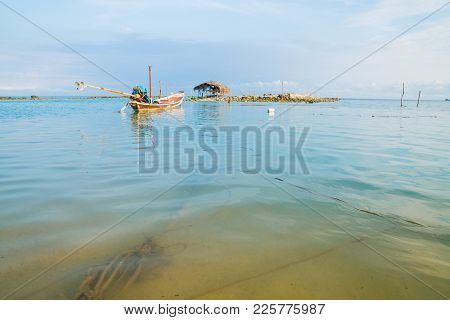 Asian Idyllic Picturesque Coastal Scene With Traditional Long Tail Fishing Boat With Knotted Mooring