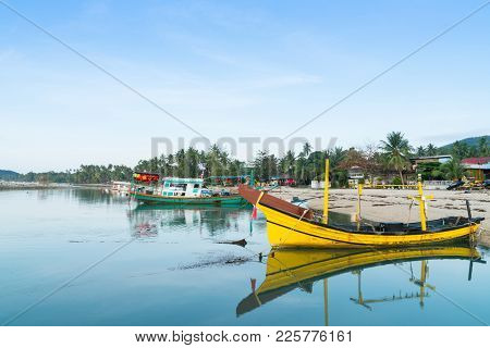 Fishing Boats Including Bright Yellow Traditional  Wooden Boat Reflected And Moored On Bang Kao Beac
