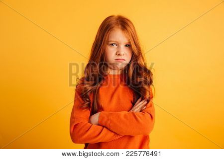 Photo of displeased little redhead girl with freckles standing isolated over yellow background. Looking camera with arms crossed.