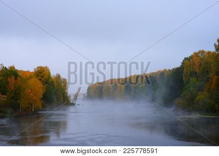 A White Mist Rises Above The River In The Autumn Forest. Beautiful Views Of The Autumn Landscape In