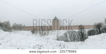 Fortress Wall Of Smolensk In The Winter Fog. Part Of The Fortress Wall And Tower In Winter. Along Th