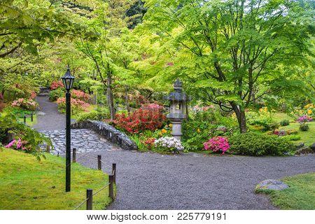 Stone Bridge And Lantern Along Walking Path In A Japanese Garden.