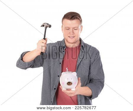 Young man holding hammer over piggy bank on white background