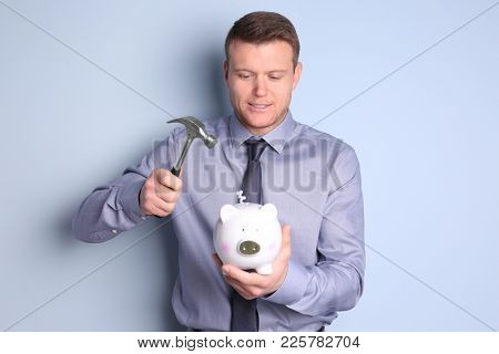 Young man holding hammer over piggy bank on color background