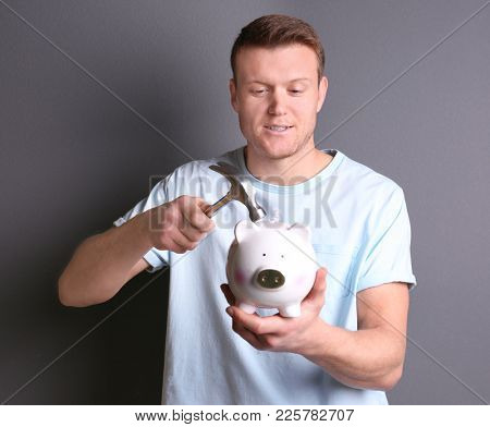 Young man holding hammer over piggy bank on grey background
