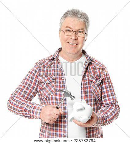 Mature man holding hammer over piggy bank on white background