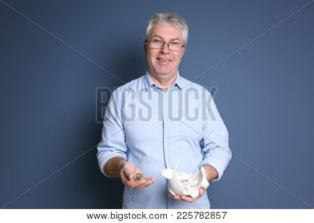 Mature man holding broken piggy bank with coins on color background