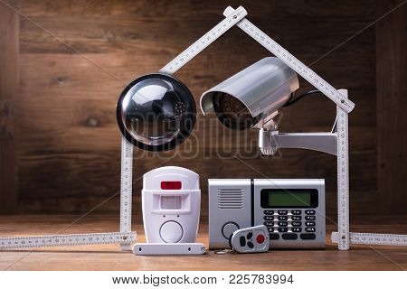 Cctv Camera And Security Alarm System Under The House Made With Measuring Tape