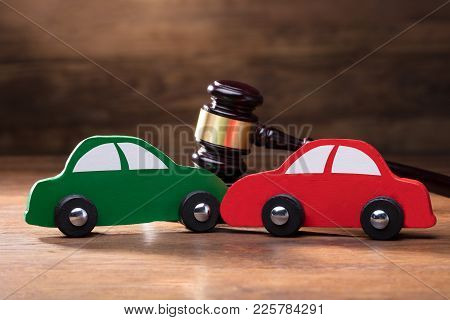 Collision Of Wooden Two Toy Cars In Front Of Gavel On The Wooden Table