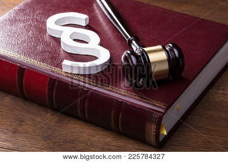 Close-up Of Big White Paragraph Symbol, Mallet And Law Book On Wooden Table