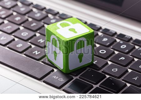 Close-up Of Lock Symbol On Green Wooden Block Over The Laptop Keypad