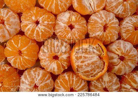 Bright Yellow Design Background Of Round Peeled Tangerines, One Fruit Half In Orange Peel.