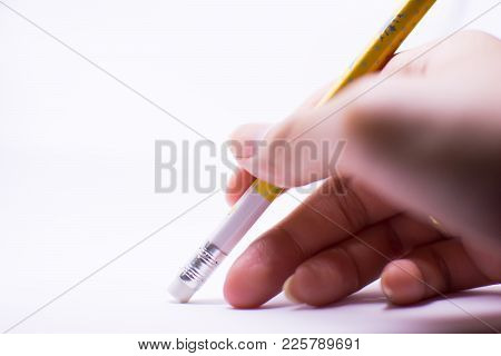 A Woman's Hand Is Erasing Something With The Rubber Sticking With The Pencil On The White Background