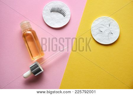 Bottle of oil and cotton pads with false eyelashes on color background
