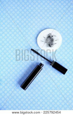 Mascara and cotton pad with false eyelashes on color background