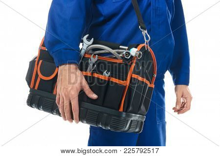 Young plumber in uniform with tool bag on white background